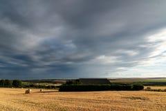 Beautiful Summer landscape of field of hay bales with dramatic s. Beautiful moody Summer landscape of field of hay bales with dramatic stormy clouds overhead in Stock Photo