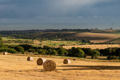 Beautiful Summer landscape of field of hay bales with dramatic s. Beautiful moody Summer landscape of field of hay bales with dramatic stormy clouds overhead in Royalty Free Stock Photos