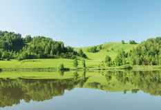 Beautiful summer landscape with green hills reflected in waterl Royalty Free Stock Photo