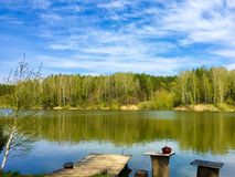 Lake landscape. Bright colors. Wooden pier on the lake, household items for outdoor recreation. stock image