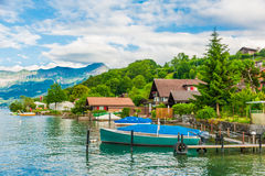 Beautiful summer landscape with lake, mountains, houses and a boat Stock Image