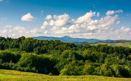 Mountain ridge with high peak behind the forest. Beautiful summer landscape. mountain ridge with high peak behind the forest. lovely sky with clouds stock image