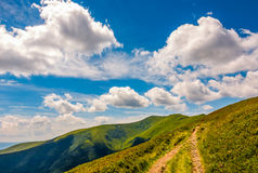 Beautiful summer landscape in mountains. Fine weather with blue sky and some clouds. gorgeous travel background with footpath through the mountain ridge Royalty Free Stock Photos
