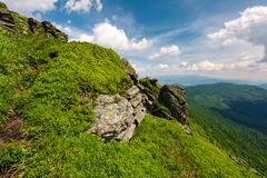 Beautiful summer landscape in mountains. View from the hillside in to the valley and nearby ridge under the cloudy sky Royalty Free Stock Image