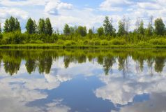 Beautiful summer landscape with reflection of clouds in the rive Royalty Free Stock Photos