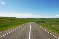 Beautiful summer landscape with a straight asphalt motorway going among green hills. In a sunny day stock image