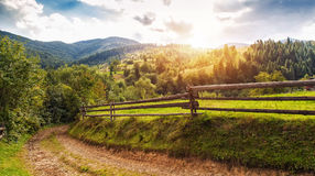 Beautiful summer landscape with wooden fence and mountains. blue. Sky and green heels of ukrainian Carpathians Royalty Free Stock Image