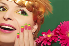 Beautiful summer makeup. Beautiful summer makeup with pink lips and colorful nails on a beautiful young girl with braids on his head and near the pink gerberas stock images