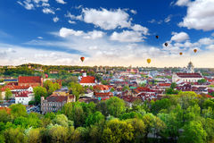 Beautiful summer panorama of Vilnius old town with colorful hot air balloons in the sky Royalty Free Stock Image