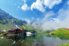 Beautiful summer scenery around balea lake. Grassy meadows and low clouds around. popular travel destination. location fagaras mountains, romania, europe stock image