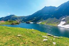 Beautiful summer scenery around balea lake. Grassy meadows and rocky ridge around. popular travel destination. location fagaras mountains, romania, europe stock images