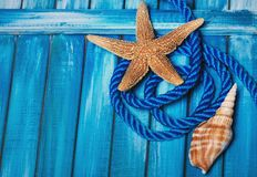 Beautiful summer sea background. Blue wooden boards, blue decorative rope, seashells. Stock Photo