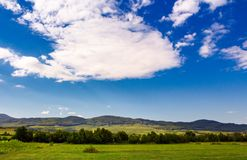 Beautiful summer sky over the mountainous area. Lovely countryside with forested hills and fields Stock Photos