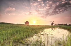 Beautiful summer sunrise over windmill by river Stock Photography