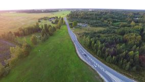 Beautiful summer sunset. Cars on country road. Green forest. Aerial fo stock video