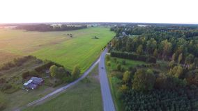 Beautiful summer sunset. Cars on country road. Green forest. Aerial fo. Beautiful summer sunset. Green fields and forest. Aerial footage stock footage