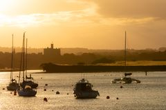 Beautiful summer sunset landscape in Amble town, Northumberland, UK. Yellow and orange sky above water and. Marina, Warkwoth Castle in background royalty free stock photo