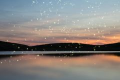 Stunning Summer sunset landscape of fireflies glowing above vibrant lake and hills in distance royalty free stock images