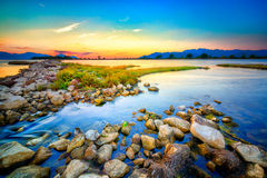 Beautiful summer sunset over the rocky shore by the sea Stock Photo