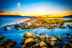 Beautiful summer sunset over the rocky shore by the sea Royalty Free Stock Images