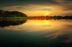 Beautiful summer sunset at the river with blue sky, red and orange clouds, green trees and water Royalty Free Stock Images
