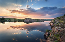 Beautiful summer sunset at the river with colorful sky Stock Photos