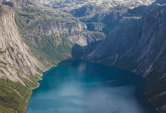 Beautiful summer vibrant view on famous Norwegian tourist place - trolltunga, the trolls tongue with a lake and mountains, Norway,. Trolltunga - famous rock Stock Photography