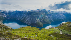 Beautiful summer vibrant view on famous Norwegian tourist place - trolltunga, the trolls tongue with a lake and mountains, Norway,. Trolltunga - famous rock Stock Photo
