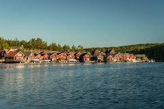 Summer view of a Swedish fishing camp by the water. Beautiful summer view of a fishing camp on the Swedish north east coast. With small red buildings in a row stock photography