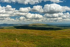 Summer view across the Swedish fjeld world. Beautiful summer view over the Swedish mountains or fjeld word in Northern Sweden with blue sky and fluffy white royalty free stock images
