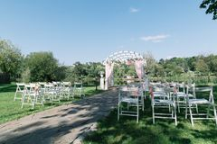 Beautiful summer wedding ceremony outdoors. Decorated chairs stand on the grass. Wedding arch made of light cloth and white and pi. Nk flowers on a green natural Stock Photo