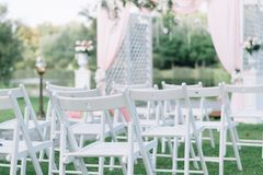 Beautiful summer wedding ceremony outdoors. Decorated chairs stand on the grass. Wedding arch made of light cloth and white and pi. Nk flowers on a green natural Stock Photos