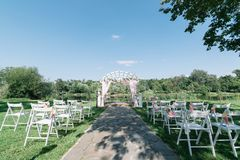 Beautiful summer wedding ceremony outdoors. Decorated chairs stand on the grass. Wedding arch made of light cloth and white and pi. Nk flowers on a green natural Stock Photography