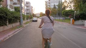 Beautiful summertime mood shot of young woman riding bicycle in stylish outift, pedalling in sunset light stock video footage