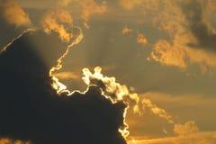 Beautiful sun beams that borders a dark cloud Stock Photos