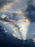 Beautiful Sun beams coming from sun hidden behind clouds with blue vibrant sky Stock Photography