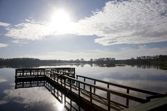 Fishing pier on a blue sky day. A beautiful sun behind clouds at a green fishing pier or wharf Royalty Free Stock Image