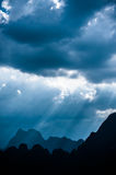 Beautiful sun rays through the clouds over mountains,evening lig Royalty Free Stock Photo
