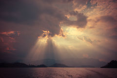 Beautiful sun rays through the clouds over mountains,evening lig Royalty Free Stock Image