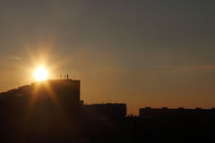Beautiful sun during sunset over roofs of residential buildings Stock Photos