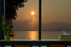 Beautiful sundown over the mountain and the lake in the window view. With table of resort royalty free stock photo