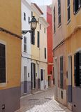 A beautiful sunlit narrow cobbled quiet street of old houses painted typical bright colors in ciutadella menorca royalty free stock photo