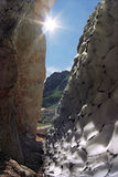 Beautiful sunny abstract rocky mountain scenery with a cleft between snow and rock Royalty Free Stock Image