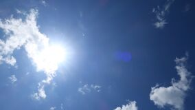 Beautiful sunny blue sky with bright sun light shining through white clouds
