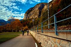 Beautiful sunny day in Austrian alps mountains. Two men on bikes in alps riding from Hallstatt Obertraun train station. In mountains. Location: resort village stock image