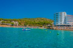 Beautiful sunny day in Sant Elm, with a beautiful blue water in Majorca, with some building in the horizont and people Stock Photography