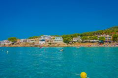 Beautiful sunny day in Sant Elm, with a beautiful blue water in Majorca, with some building in the horizont and people Stock Image