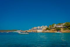 Beautiful sunny day in Sant Elm, with a beautiful blue water in Majorca, with some building in the horizont and people Stock Photo