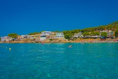Beautiful sunny day in Sant Elm, with a beautiful blue water in Majorca, with some building in the horizont and people Royalty Free Stock Photo