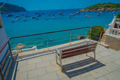 Beautiful sunny day in Sant Elm, with a public chair to enjoy the view in Majorca, with people enjoying the water, in Royalty Free Stock Image